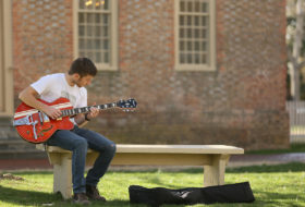 Male student playing guitar on a bench near the Wren Building