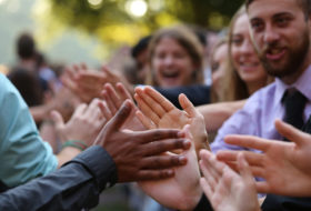 Lots of hands and smiling faces high-fiving during Opening Convocation