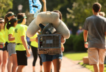 Student carrying a tall stack of dorm supplies during Move-In