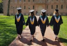 Four students wearing caps and gowns hold hands as they stroll down a brick path