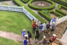Aerial view of students standing near a fenced garden on Somerset Place Plantation
