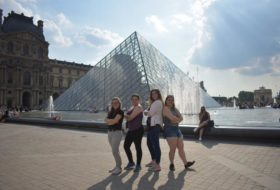 Four friends pose in front of the glass pyramid at the Louvre museum in Paris.