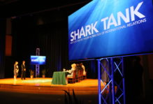 Shark Tank sign on a screen on a stage with people presenting in the background