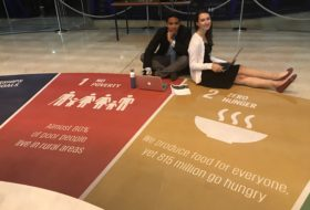 Lauren Hobbs and Josh Panganiban sitting on a floor with a large graphical chart
