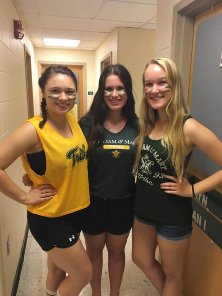 Three smiling students posing in Tribe gear in a residence hall.