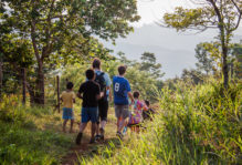 Students Allie Cooper, Noah Scruggs and Sophie Harris walk with a group of Guatemalan children near a rural community.