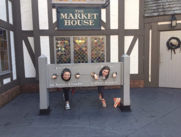 "Two female students with their heads inside colonial style stocks at Busch Gardens. The stocks read, left to right, ""The Cost of an Untidy Chamber"" and ""for Want of a Quiet Tongue""."