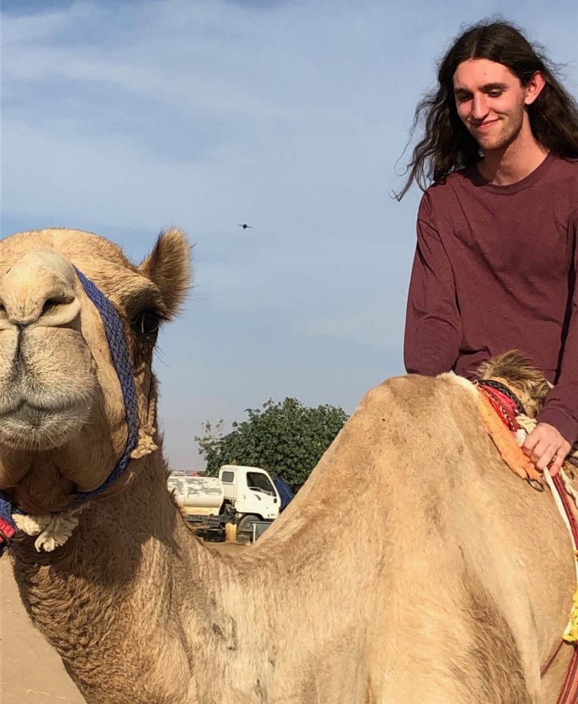 Finn Mayhew goes for a ride on a camel