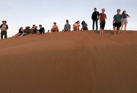 William & Mary's Oman scholar-adventurers watching the sunset in the Sharqiya Sands.