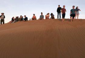 William & Mary's Oman scholar-adventurers watching the sunset in the Sharqiya Sands.
