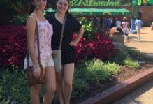 two girls pose in front of a bush with a cut-off view of the Busch Gardens sign in the backdrop