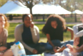 Four college seniors sit outside enjoying a picnic and time together.