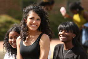 Female students at William & Mary smile for the camera at Sneak Peek - a multicultural admission event on campus each spring.