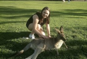 W&M student Dani Greene bending over to pet a resting kangaroo