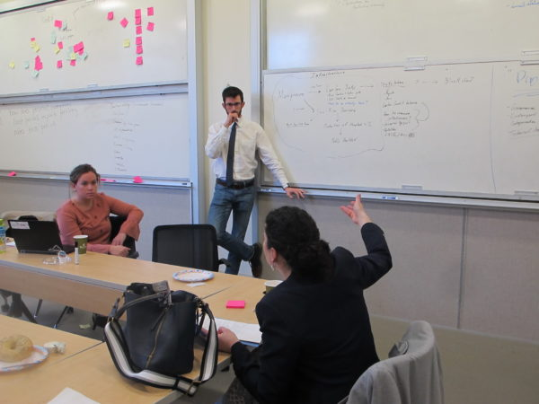 Three students in a discussion in a room with tables and whiteboards