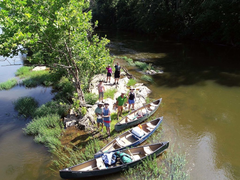 The Gladstone Gladiators pictured from the drone on a strip of sandy and treed land in the James River, standing next to their three packed canoes.