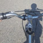 View of bike handlebars from the rider's perspective. Rider's shadow is visible on the road ahead.