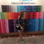 Katie in front of a wall of large colorful books