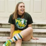 Lauren wearing Athletics branded clothing and green and gold