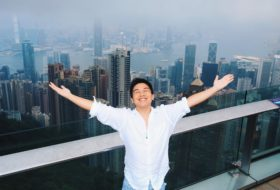 Sean at the top of a high building overlooking the city skyline