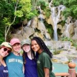 Four smiling people posing in front of a waterfall, arms around each other.