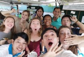 Group of ten people in a selfie making smiling and wow faces.