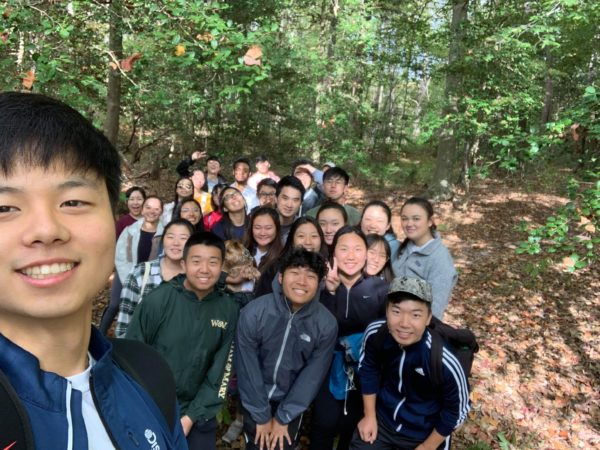 Group of nearly 30 students smiling and huddled together for a group selfie in the woods.