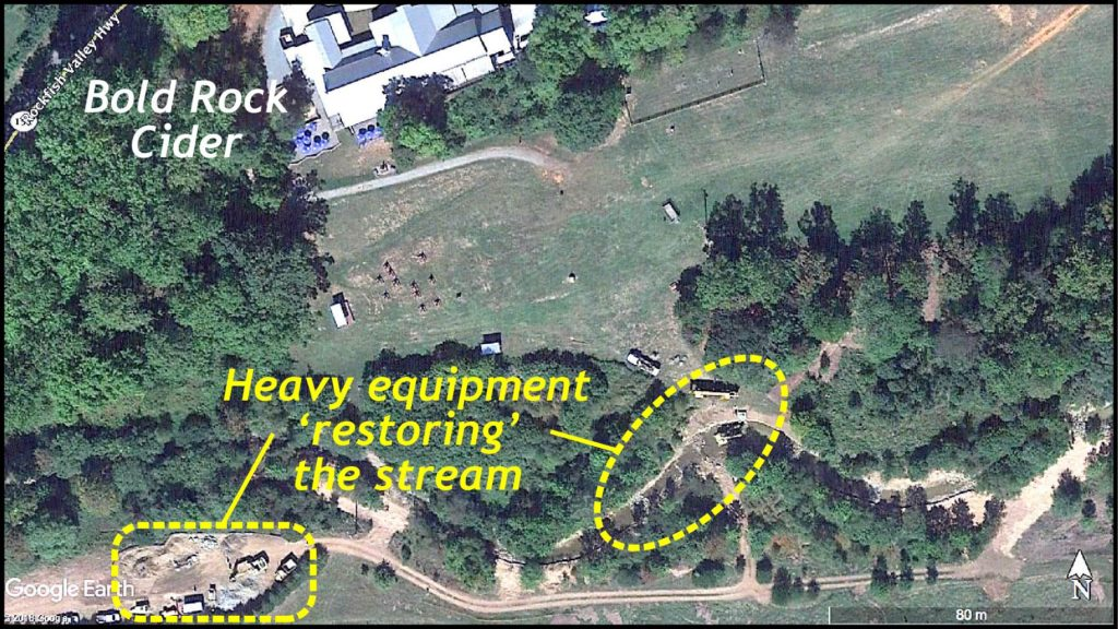 Aerial view showing equipment on dirt roads just south of the stream.