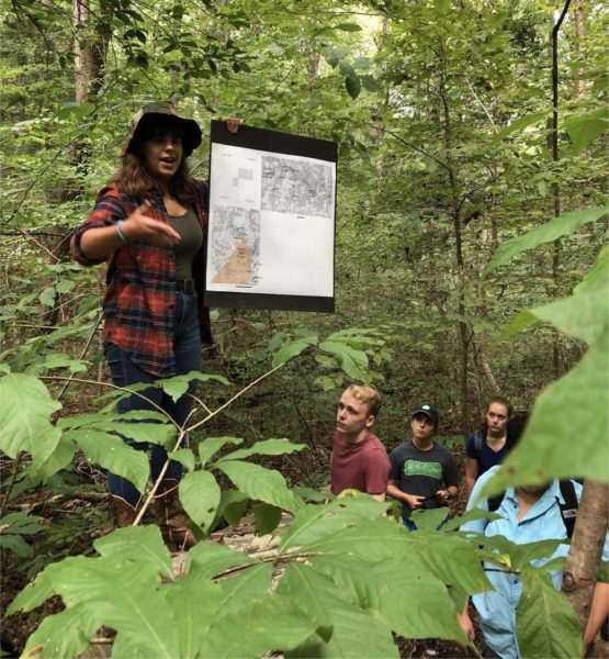 Student standing in woods pointing at poster presentation with four onlooking students below.
