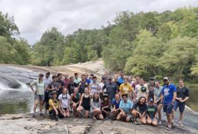 Thirty-four smiling participants group together in rugged shorts and tshirts for a photo on the gently sloping bedrock ledges of Nottoway Falls. Trees beyond the waterfall.