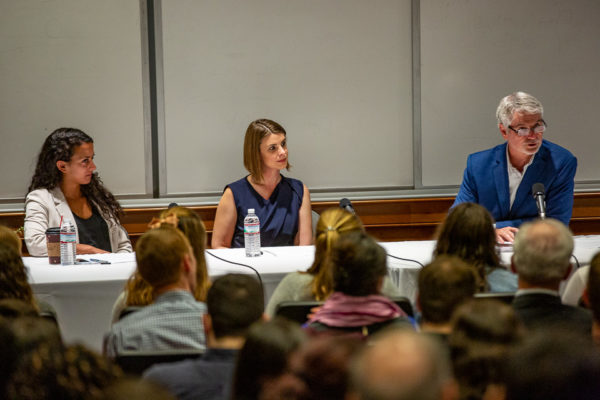 Three people sit at the front of a room at a long panel table, with microphones. Backs of audience members visible.
