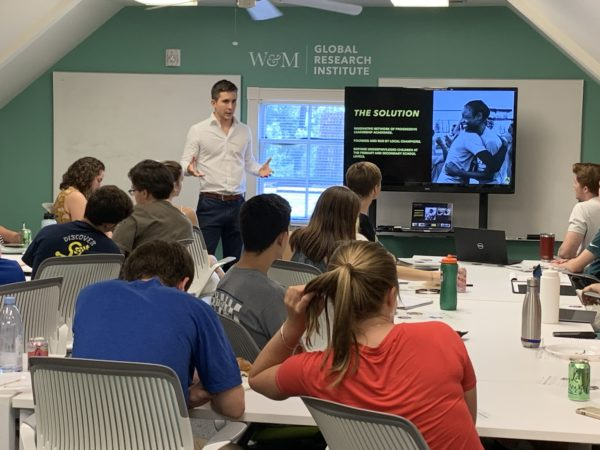 Will Smith '14 at the front of a classroom presenting to current students, with W&M Global Research Institute stenciled on the wall behind him, and The Solution on the presentation screen.