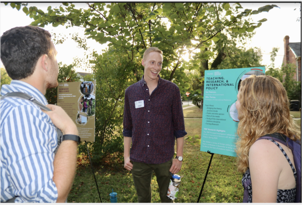 A student talking about their research to two others in front of his easel and poster board outside in the yard. Other posters visible in the background.