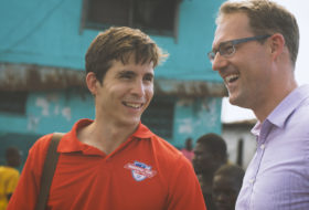 Will Smith '14 and Professor Phil Roessler smiling and talking together in Africa