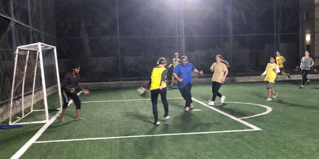 Students playing football in Ibri at night on a fenced and lighted turf field.