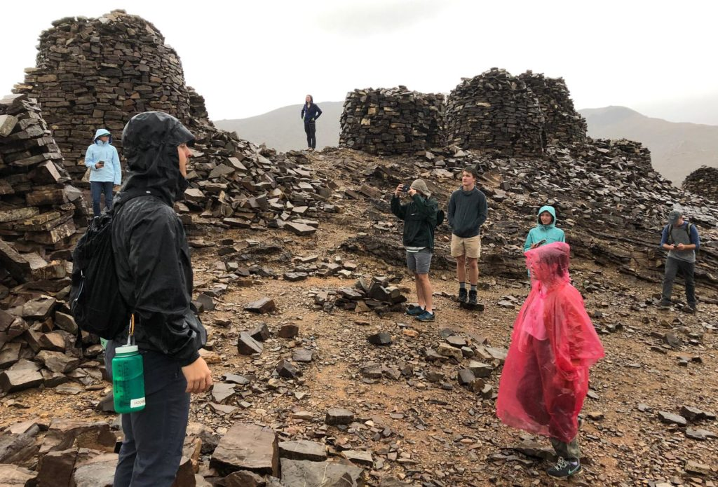 Students in rain gear at the beehive tombs of Al Ayn, Oman. Partial, rounded walls of stacked flat rocks and the same flat rocks on the ground.