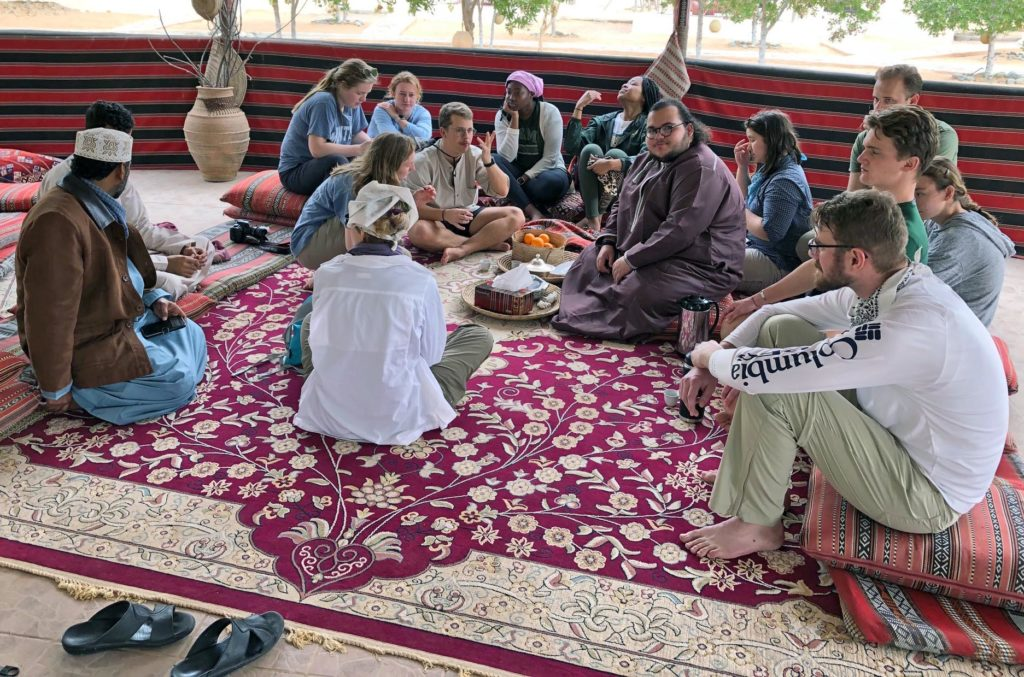 Students discussing their research at the desert camp, sitting on the floor with rugs and cushions and fruit.
