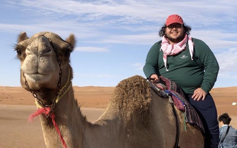 Oscar Berlanga rides a camel, smiling.