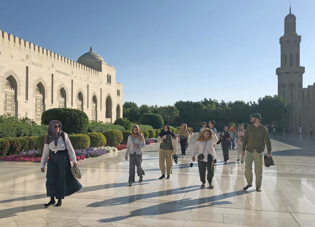 Students walking at the Grand Mosque in Muscat, Oman with green trees and gardens surrounding the grand walkways.