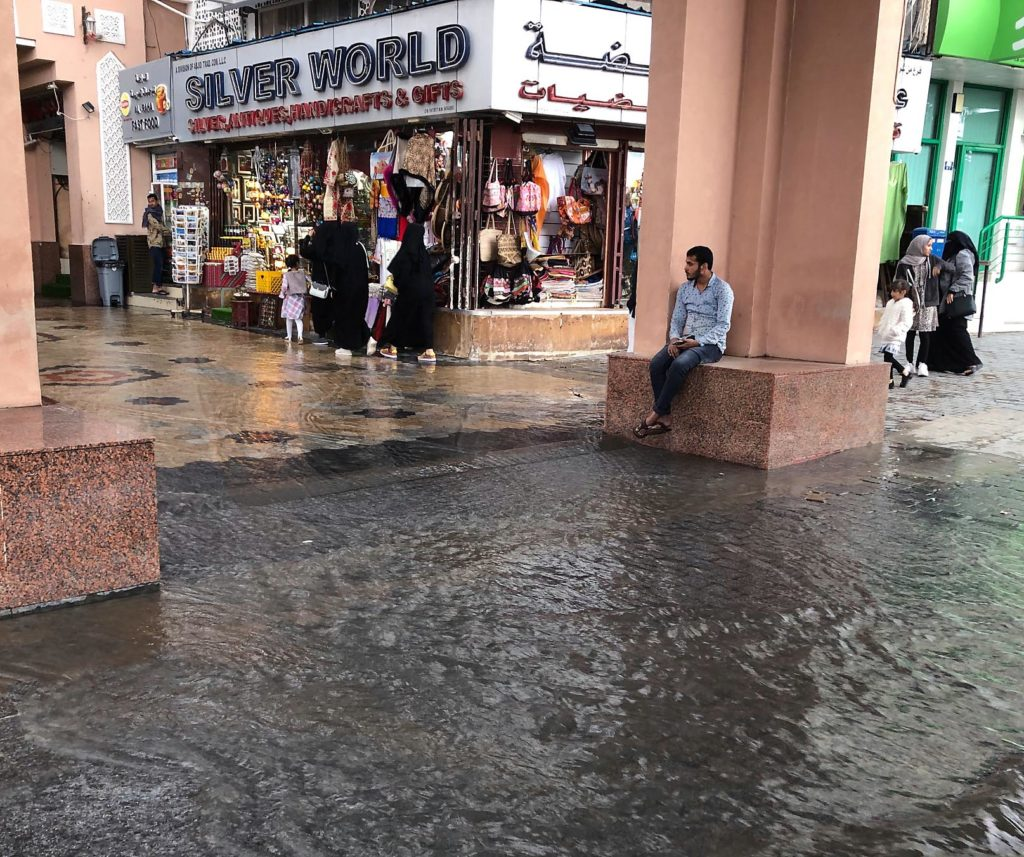 A watery and flooded Mutrah Souq with open shop fronts selling jewelry and gifts.