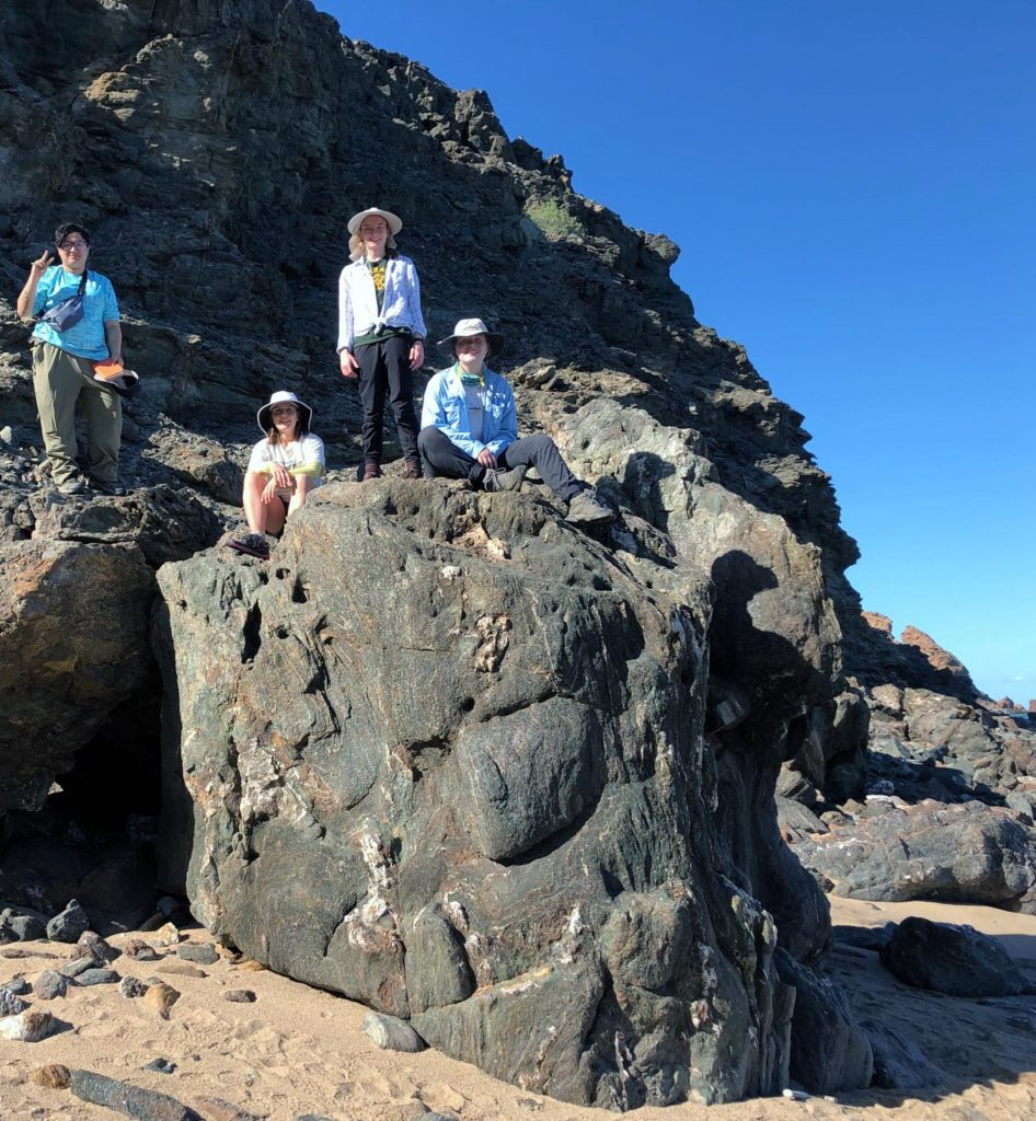 Students sitting and standing on an eclogite outcrop, Oman.
