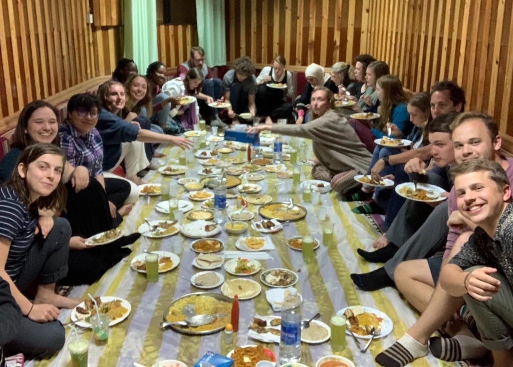 Large group of students seated on the floor and smiling around a long striped cloth filled with many dishes of food and drinks.