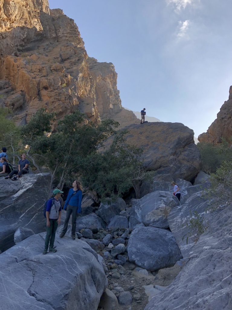 Students standing and sitting on large boulders in the channel of the Sidaq Gorge, Oman.