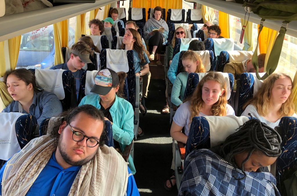 Students lounging and sleeping on a bus.