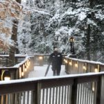 Facilities staff member using a blower on the elevated wooden paths with side rails that extend through the snowy woods.