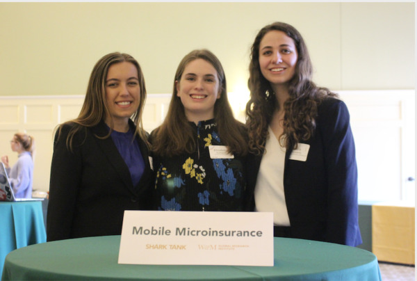 Three students in business attire standing at a table with a placard reading Mobile Microinsurance