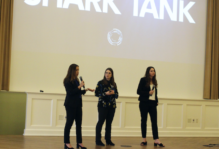 Three students in business attire on stage with microphones presenting. Slide on large screen behind them reads Shark Tank
