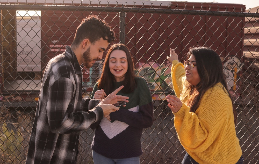Teenage boy holds smartphone next to two teenage girls