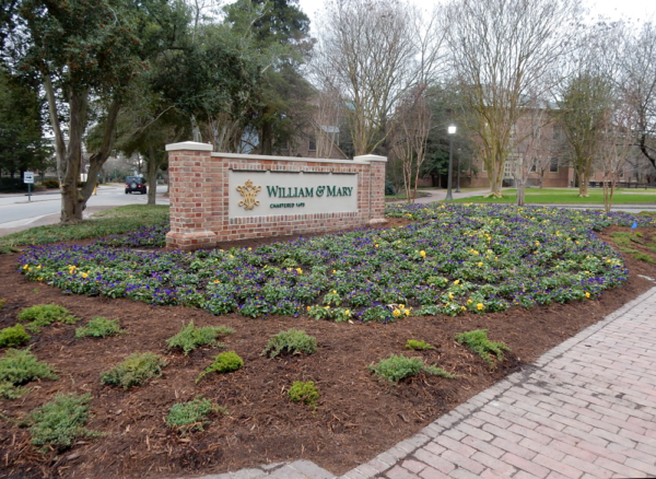 Brick and mortar William & Mary sign surrounded by mulched beds of junipers, crepe myrtles, liriope and violas