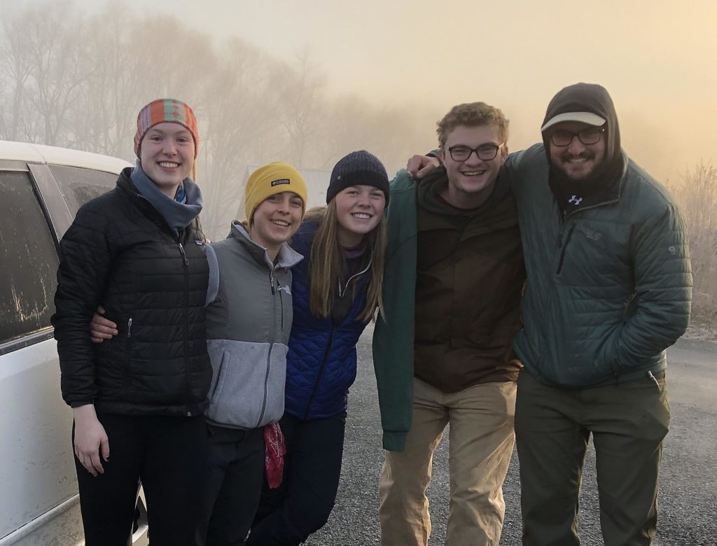 Five smiling students, posed on a foggy day in hats and jackets.